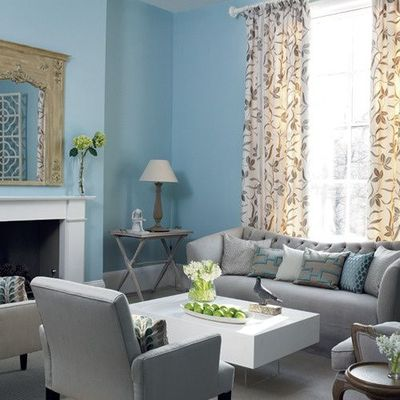 Blue and gray living room with tall floral drapes / baby ...