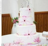 After finding a photo in a magazine, Stacey decided on a four-tiered confection iced in buttercream with white, French vanilla, and double chocolate fudge cake filled with champagne, strawberry, and chocolate hazelnut fillings. Pink and green daisies shap...