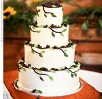Four-tiered coconut and triple-chocolate cake with buttercream frosting. Chocolate branches, fondant leaves, and blueberries give it a natural look.