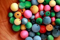 Dye wooden beads with food coloring for stringing.